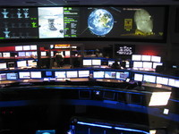 Inside JPL's space flight ops facility (sorry about the blurry picture). The Doug in the picture at the rear right is Doug Ellison. The room from which the ops team monitored the landing of all mars rovers so far (Sojourner, MER, Tango Delta Nominal MSL) is just to the left.