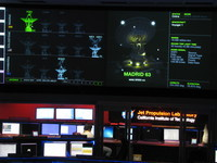 Closeup of the left background from JPL's space flight operations room, showing that the Deep Space Network's antenna in Madrid (details and picture shown) is currently talking to Voyager 1 (VGR1), and Goldstone is talking to Mars Reconnaissance Orbiter (MRO, home of HiRISE) and Mars Express (MEX).