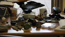 Prof. Brown's desk with several asteroid and other samples. The SciSolSys pallasite is in the plastic case in the right foreground; the SciSolSys coffee mug in the left background.