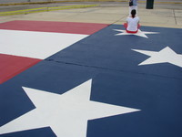 A 1:1 scale section of the US flag from the VAB for scale; each star is nearly the size of a person.