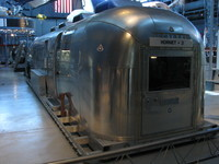 The Mobile Quarantine Facility that waited on board the USS Hornet at the conclusion of the first Moon landing, Apollo 11. The Hornet + 3 refers to the fact that they were welcoming three astronauts.