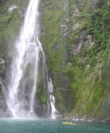 One of Milford Sound's numerous waterfalls, with some brave kayakers closing in.
